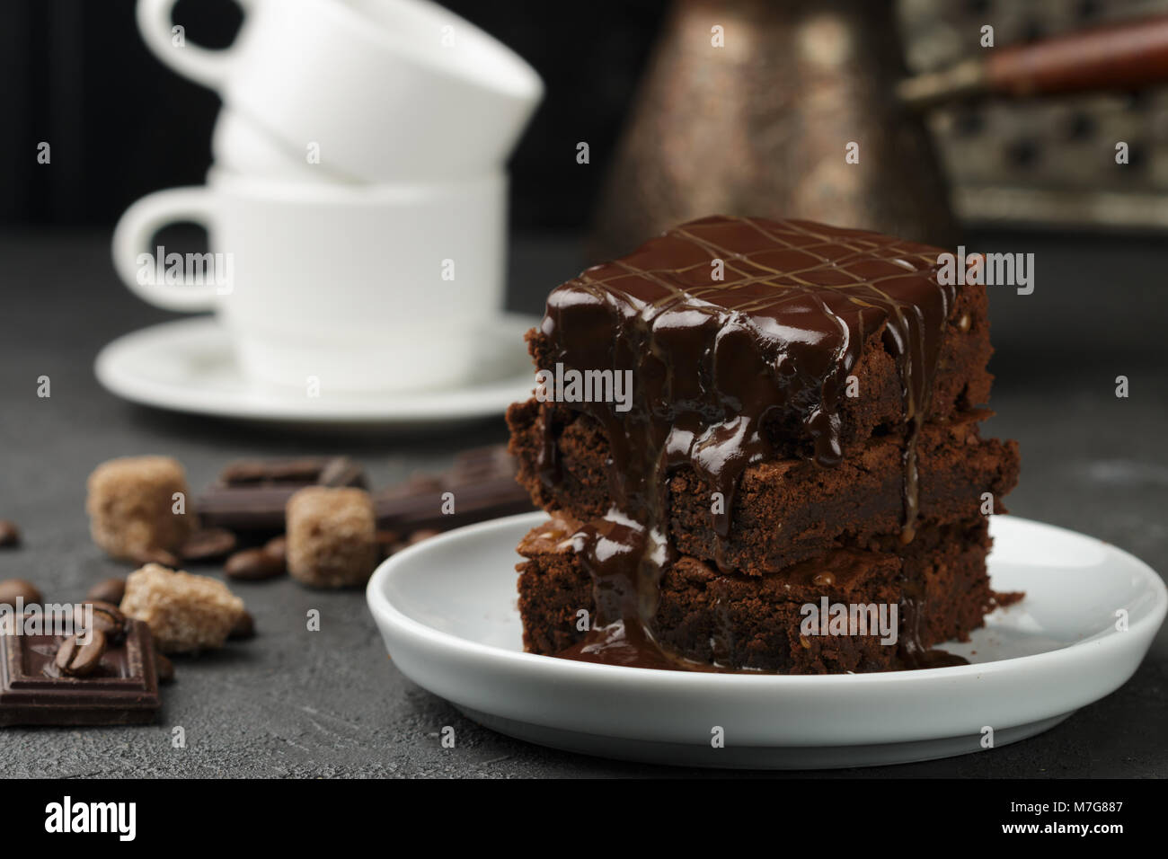 Delicious homemade brownie with chocolate sauce and caramel on the table. Selective focus Stock Photo