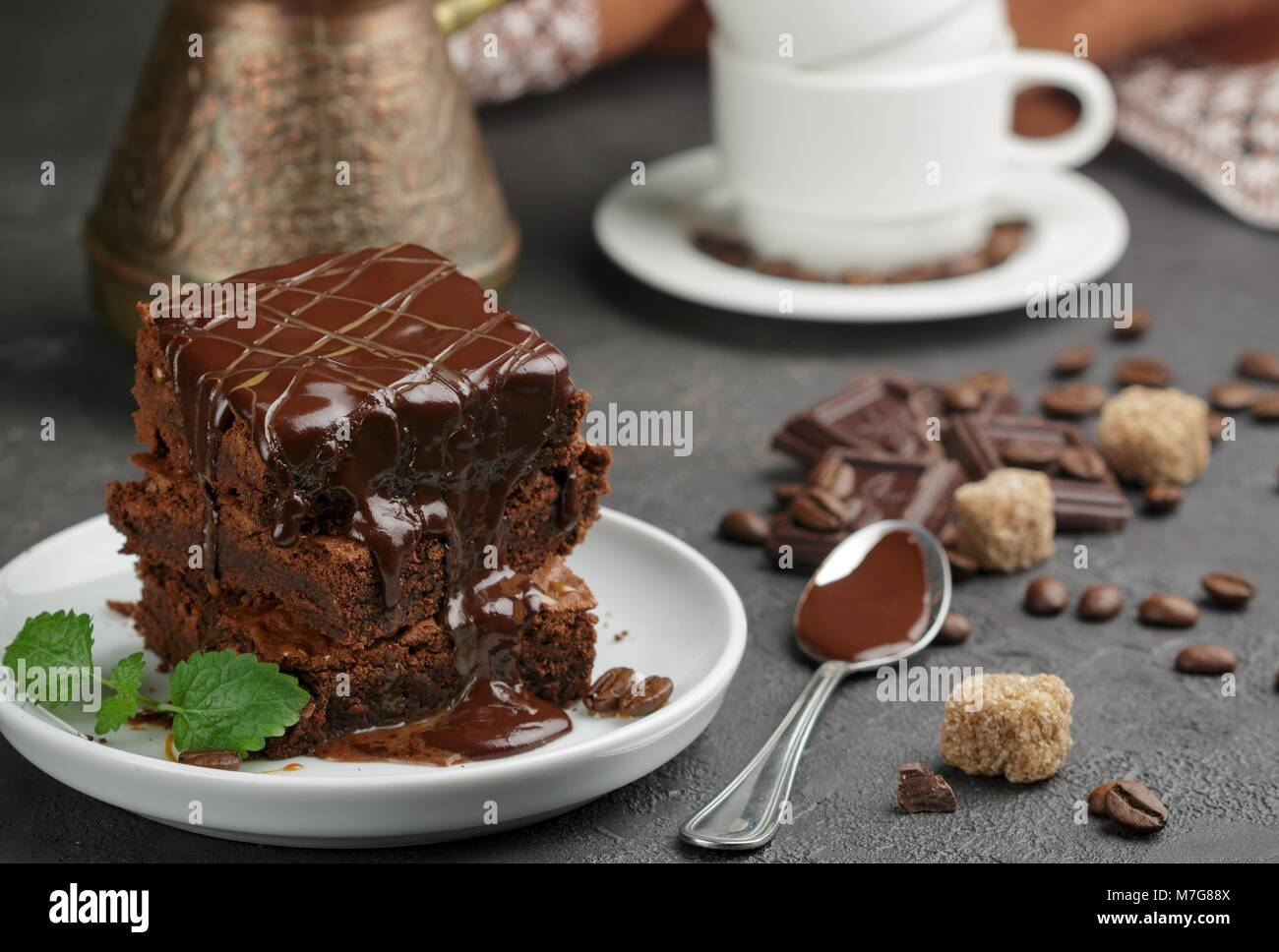 Delicious homemade brownie with chocolate sauce and caramel on the table. Selective focus - Stock Image