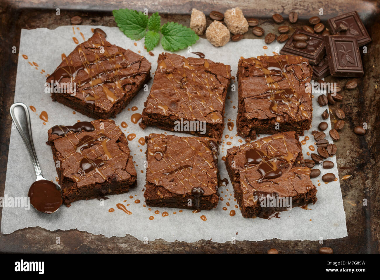 Delicious homemade brownie with chocolate sauce and caramel on the baking sheet. Top view - Stock Image