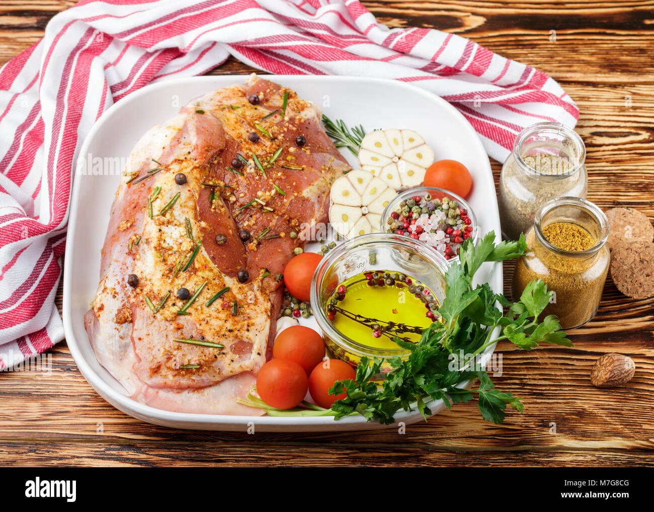 Fresh raw meat. Lamb with spices - rosemary, juniper, garlic and tomatoes in a white ceramic form on a wooden table. - Stock Image