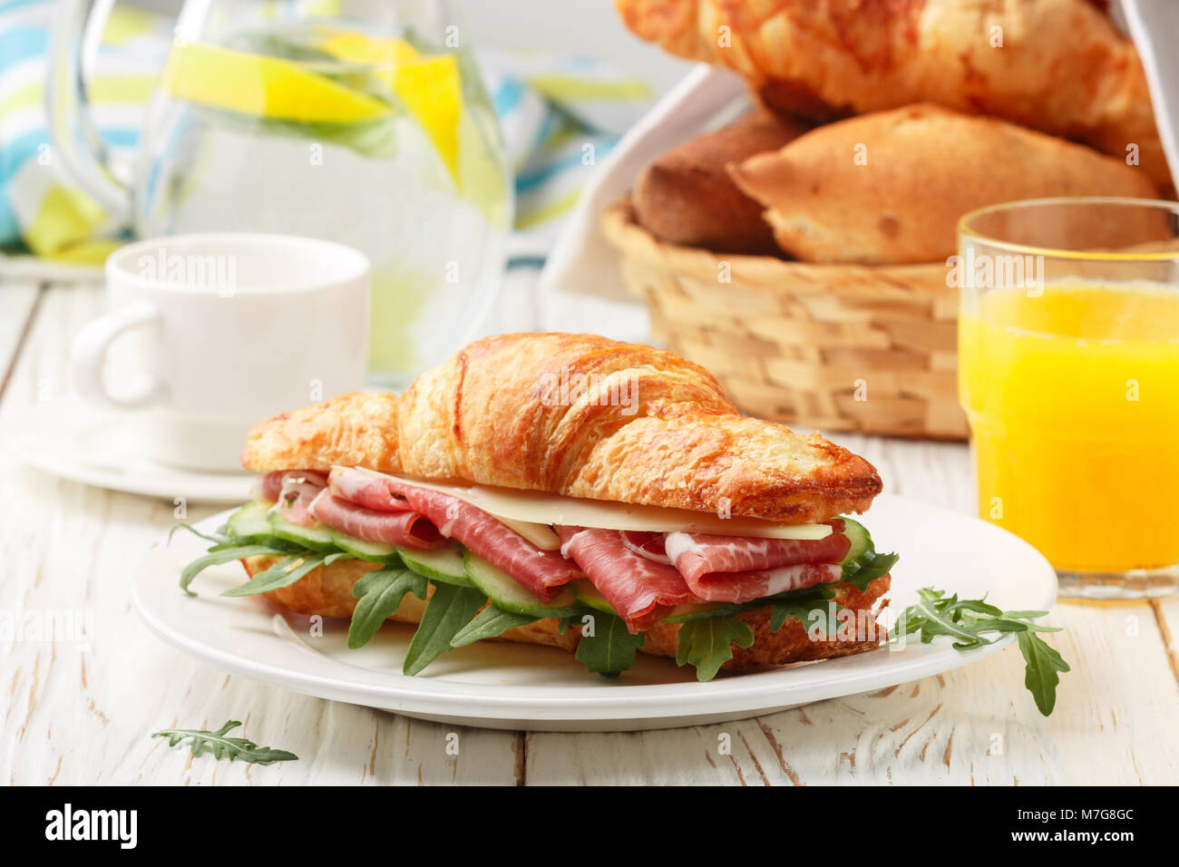 Fresh sandwich-croissant with ham, arugula, cucumber and cheese in a white plate, lemonade, orange juice and coffee - Stock Image