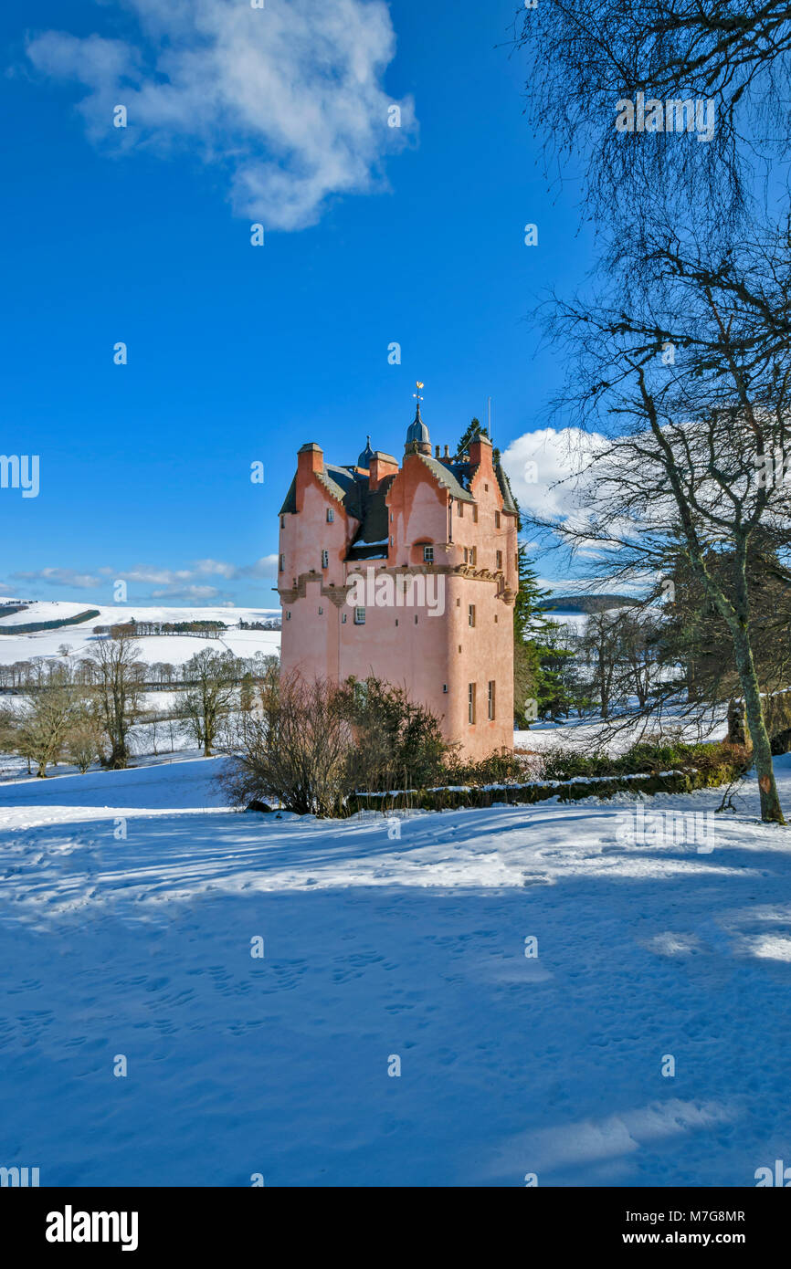 CRAIGIEVAR CASTLE ABERDEENSHIRE SCOTLAND  PINK TOWER BLUE SKY AND WINTER SNOW ON THE SURROUNDING FIELDS AND HILLS - Stock Image