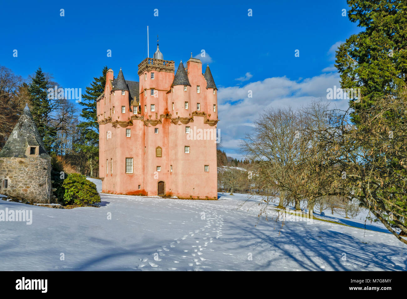 CRAIGIEVAR CASTLE ABERDEENSHIRE SCOTLAND A BLUE SKY AND FOOTPRINTS LEAD TOWARDS THE PINK TOWER SURROUNDED BY FIR - Stock Image
