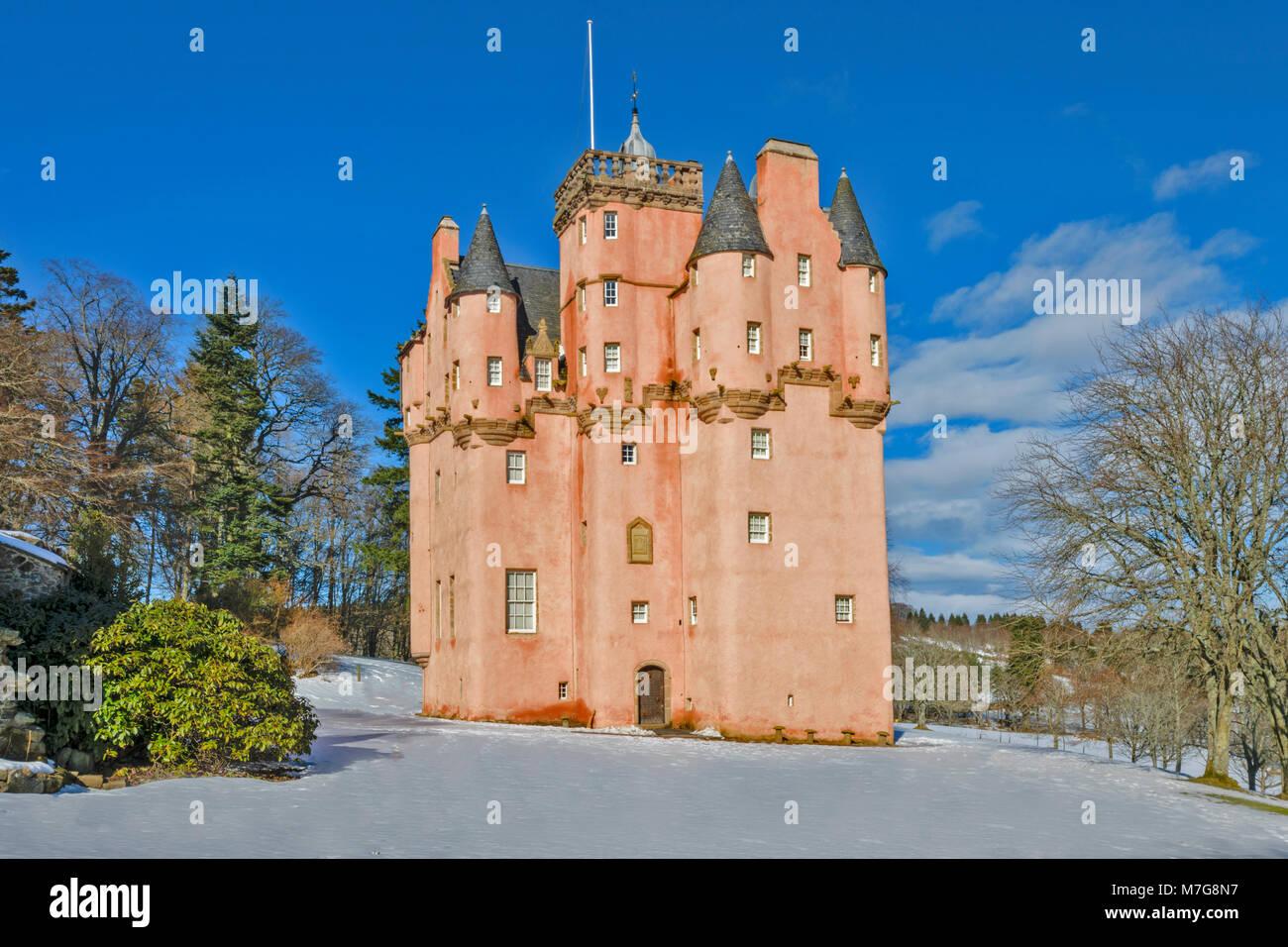 CRAIGIEVAR CASTLE ABERDEENSHIRE SCOTLAND A BLUE SKY THE PINK TOWER A SMALL GARDEN EVERGREEN FIR TREES AND DEEP WINTER - Stock Image