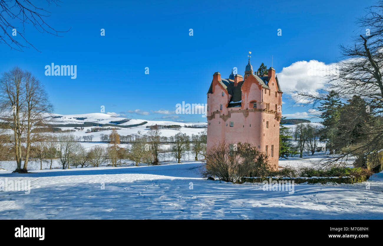 CRAIGIEVAR CASTLE ABERDEENSHIRE SCOTLAND THE PINK TOWER BLUE SKY AND SNOW ON THE SURROUNDING FIELDS AND HILLS - Stock Image