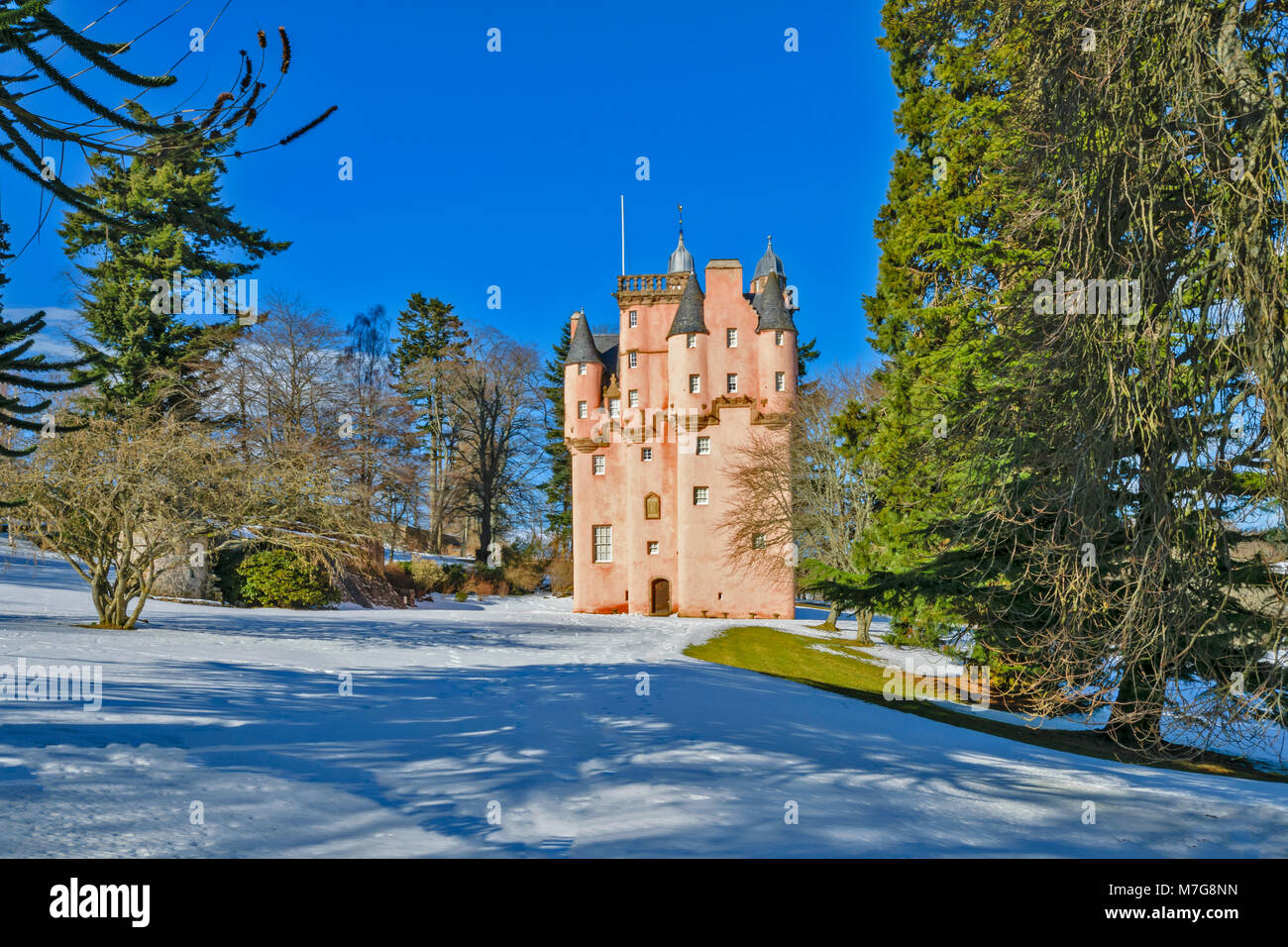 CRAIGIEVAR CASTLE ABERDEENSHIRE SCOTLAND THE PINK TOWER SURROUNDED BY EVERGREEN FIR TREES AND WINTER SNOW - Stock Image