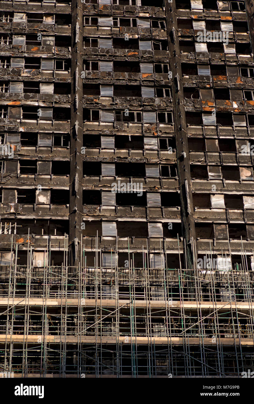 View of of burnt-out shell of Grenfell Tower housing with scaffolding, before demolition after fire disaster in - Stock Image