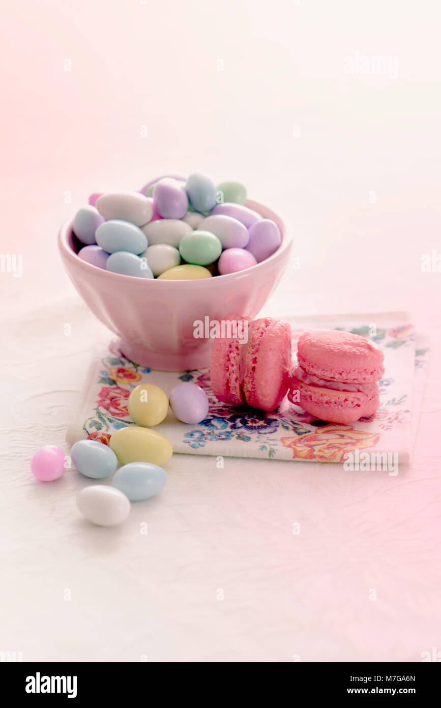 Jordan almonds and macaroons on a plain background - Stock Image