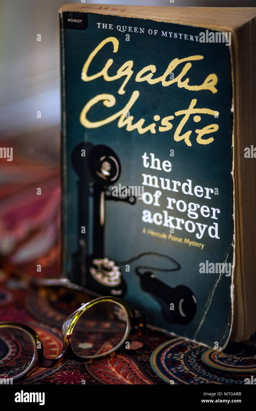 A paperback novel edition of Agatha Christie's The Murder of Roger Ackroyd sits on a paisley table cloth, behind - Stock Image