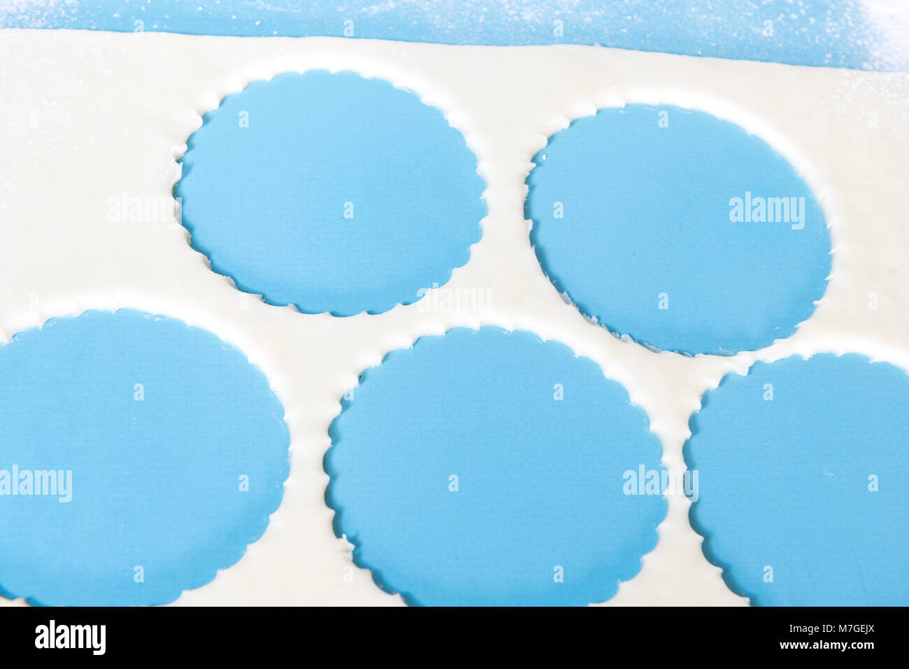 Pastry with holes home baking flour on a blue formica worktop. - Stock Image