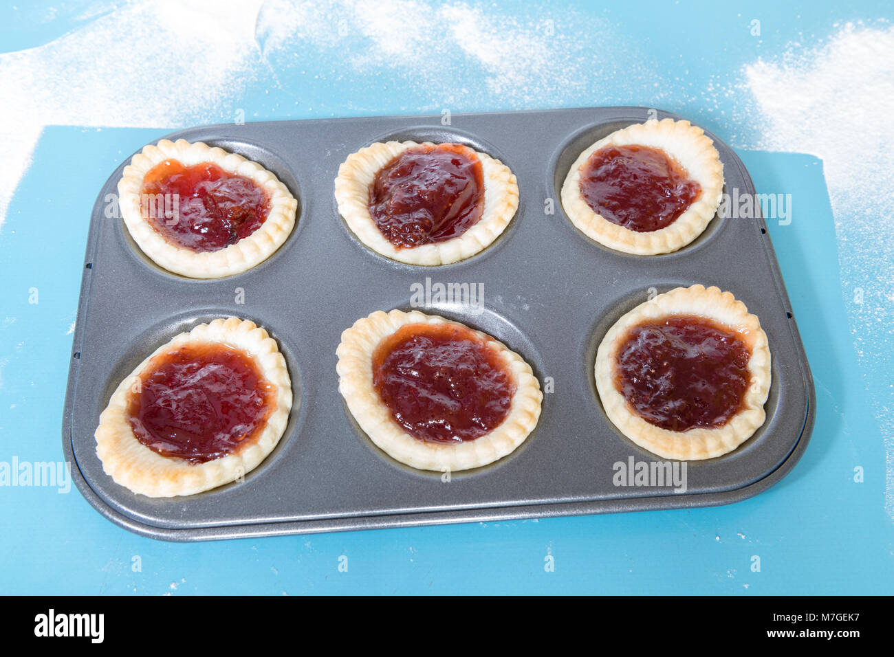 Jam tarts homemade baking tray on a blue formica worktop. - Stock Image