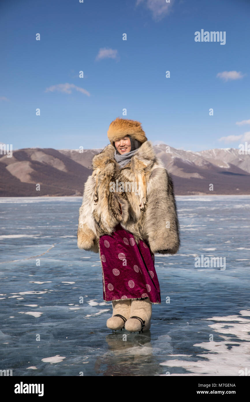 young Mongolian lady in wolfskin jacket on a frozen lake Khovsgol in northern Mongolia - Stock Image