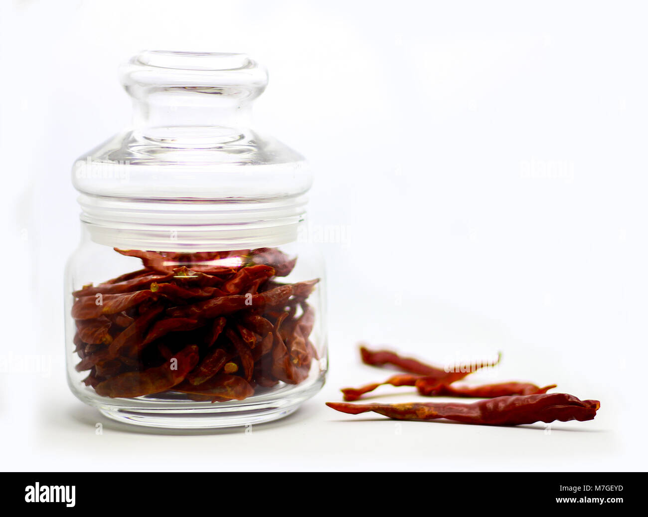 Dried Red Chilli In Glass Container in White Background - Stock Image