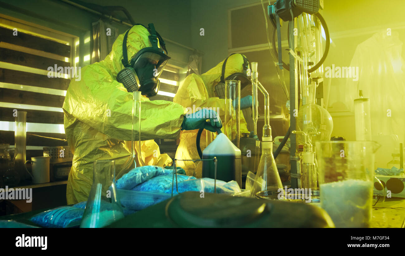 In the Underground Laboratory Two Clandestine Chemists Wearing Protective Coveralls and Masks Cook Drugs. They Work with Beakers, Distillation. Stock Photo