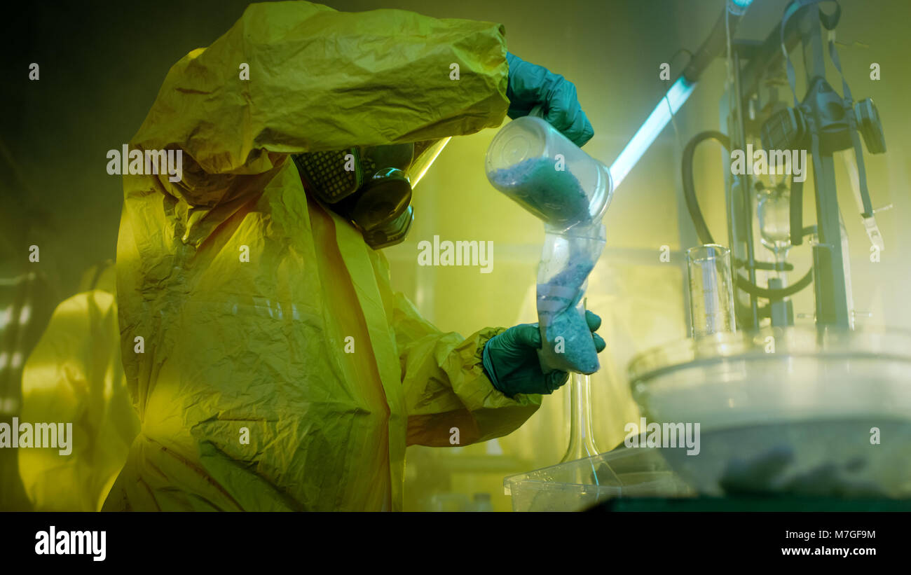In the Underground Laboratory Clandestine Chemists in Protective Masks and Coveralls Cook and Package Drugs. They Work in the Abandoned Building. Stock Photo