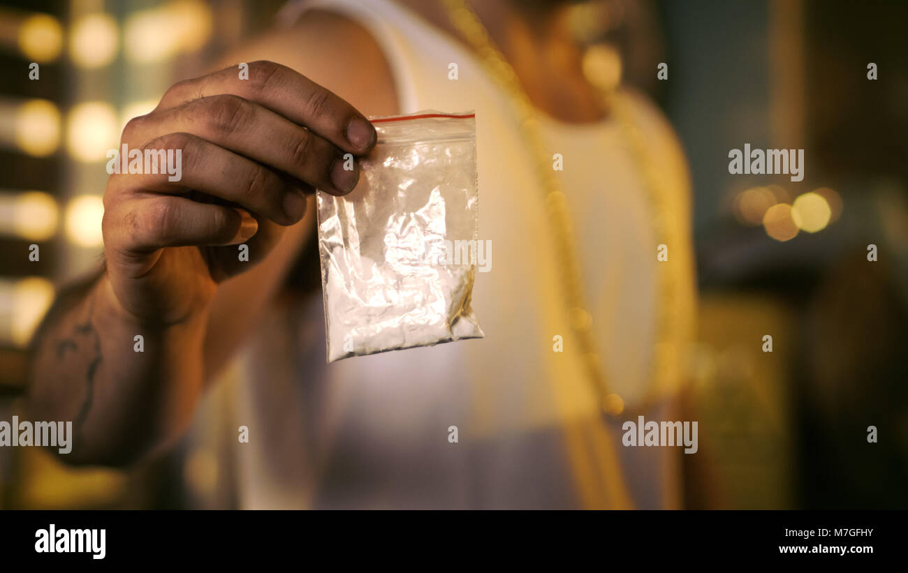 Brutal Drug Dealer Wearing Sleeveless Shirt and Gold Chain Holds and Offers Sample Bag Full of Drugs. He Lives in - Stock Image