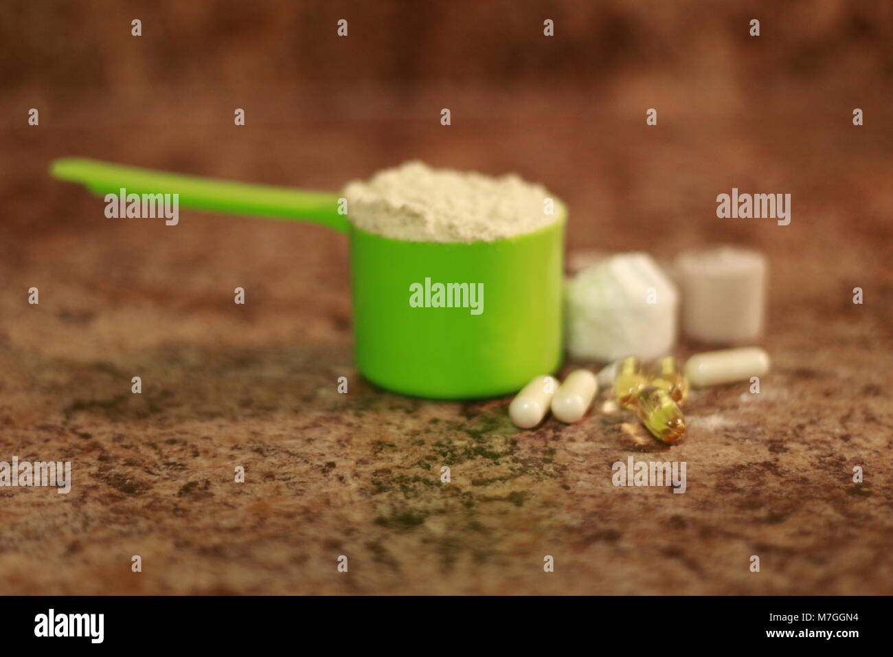 Whey protein powder in scoop with vitamins. athletes require multiple supplements to remain healthy. supplements - Stock Image