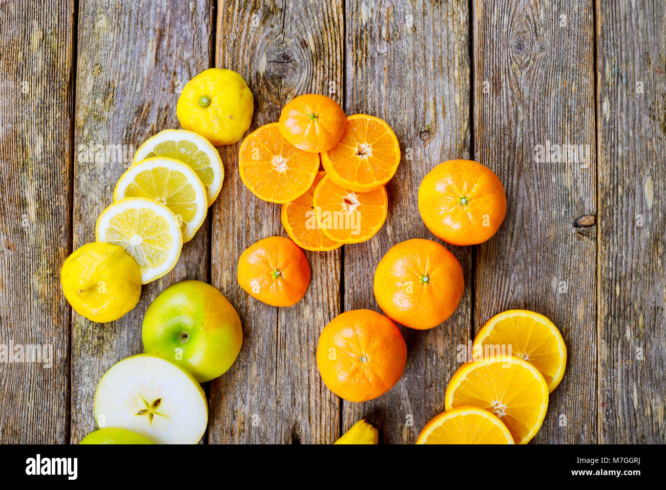 sliced citrus mix lemon grapefruit lime and orange in geometrical shapes on dark wood rustic background soft focus Stock Photo
