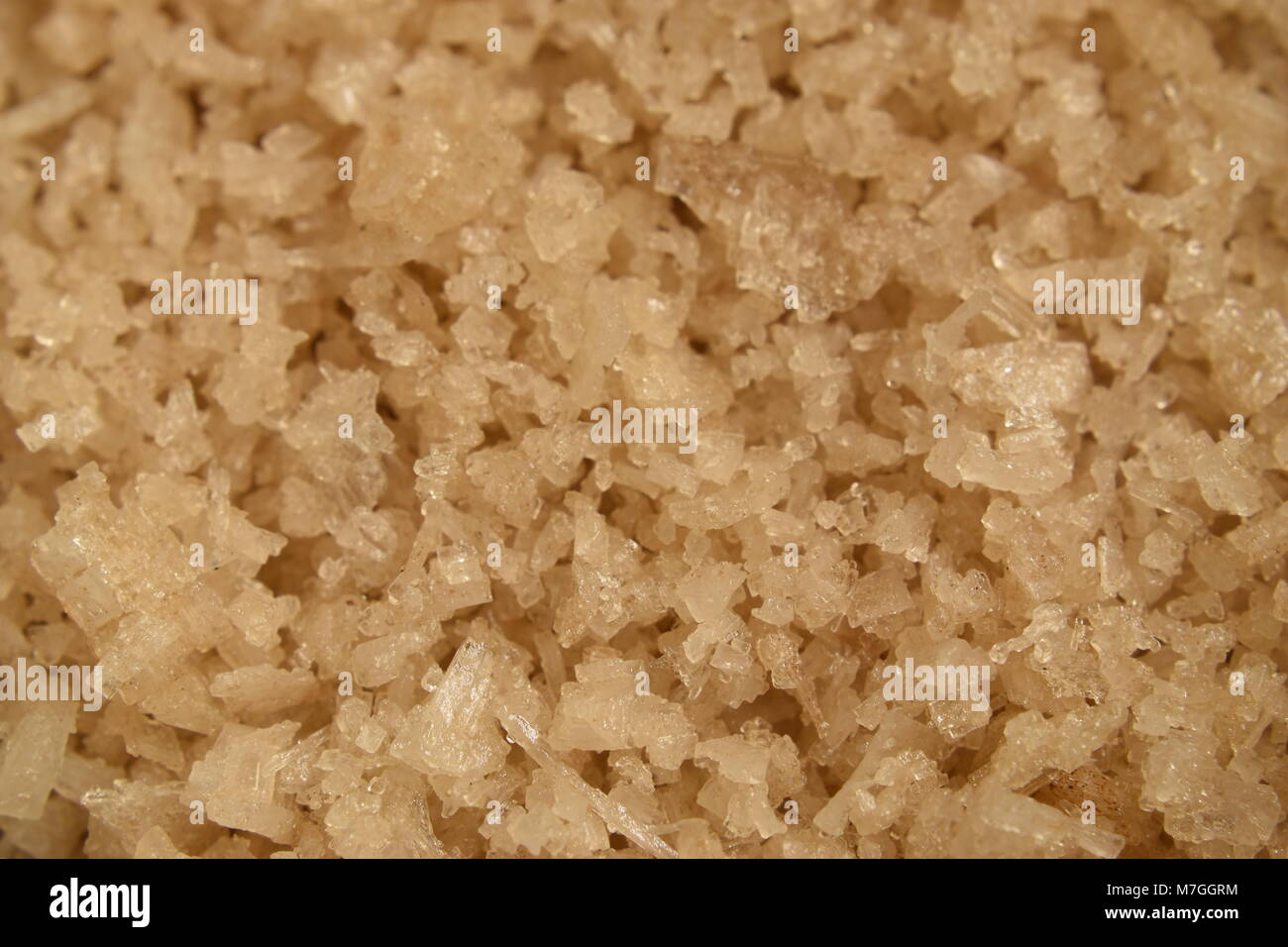 Closeup background of brown salt crystals in a heap. - Stock Image
