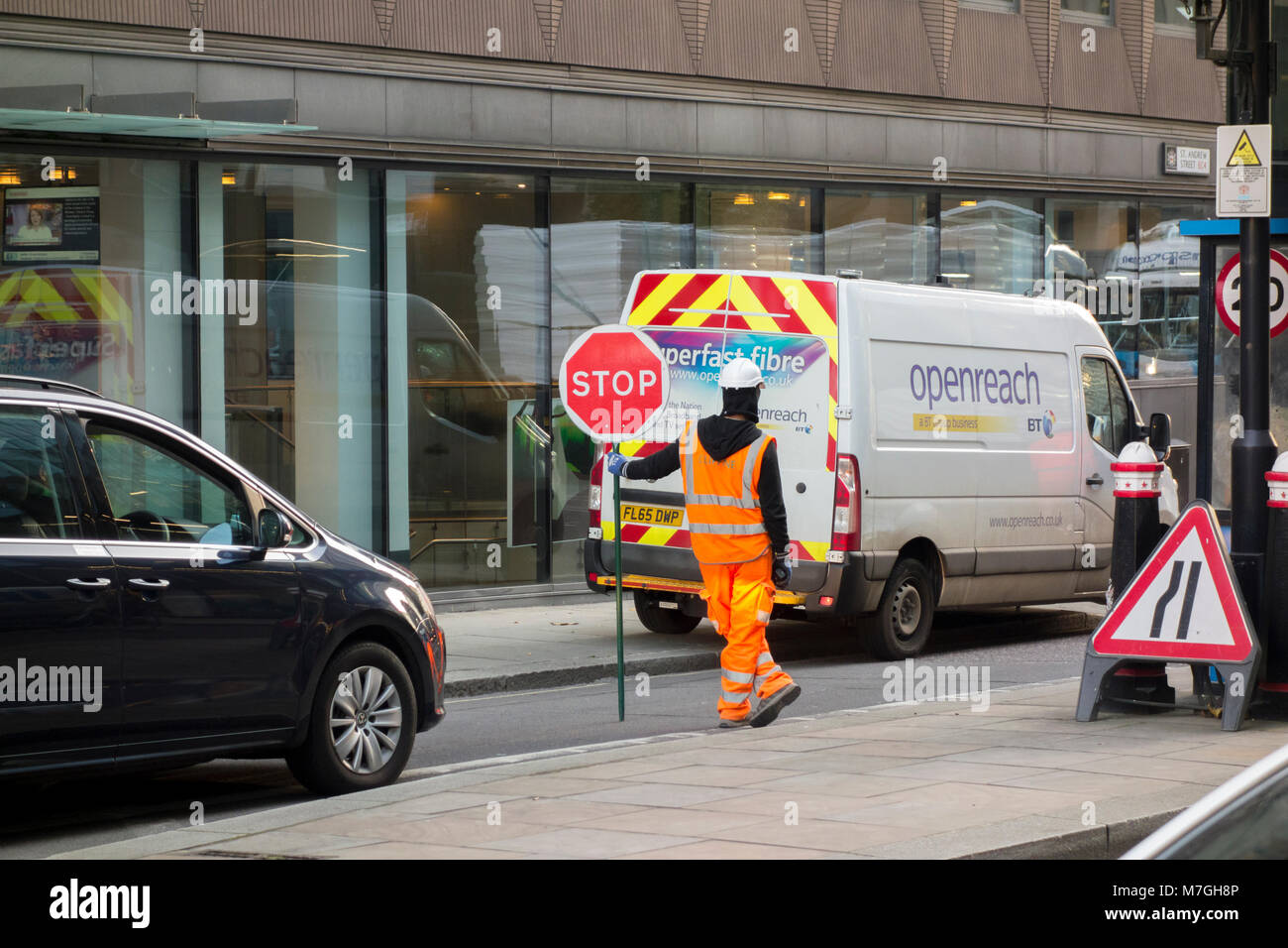 Workman in high vis holding stop sign in front of BT Openreach superfast fibre van - Stock Image