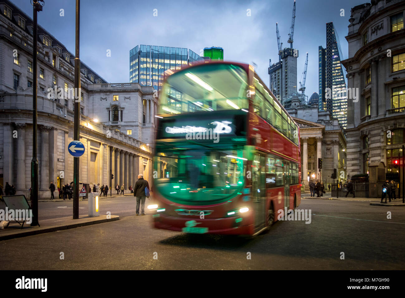 Red London bus on Bank junction at night with green traffic light illuminating front - Stock Image
