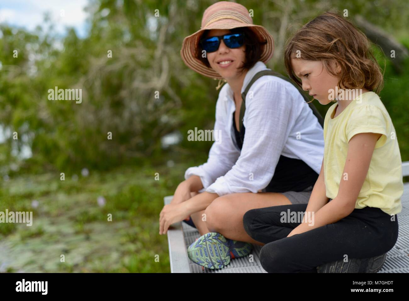 Mother and daughter sit on pier overlooking water and forest while discussing issues, Apex Park, Riverway Drive, - Stock Image