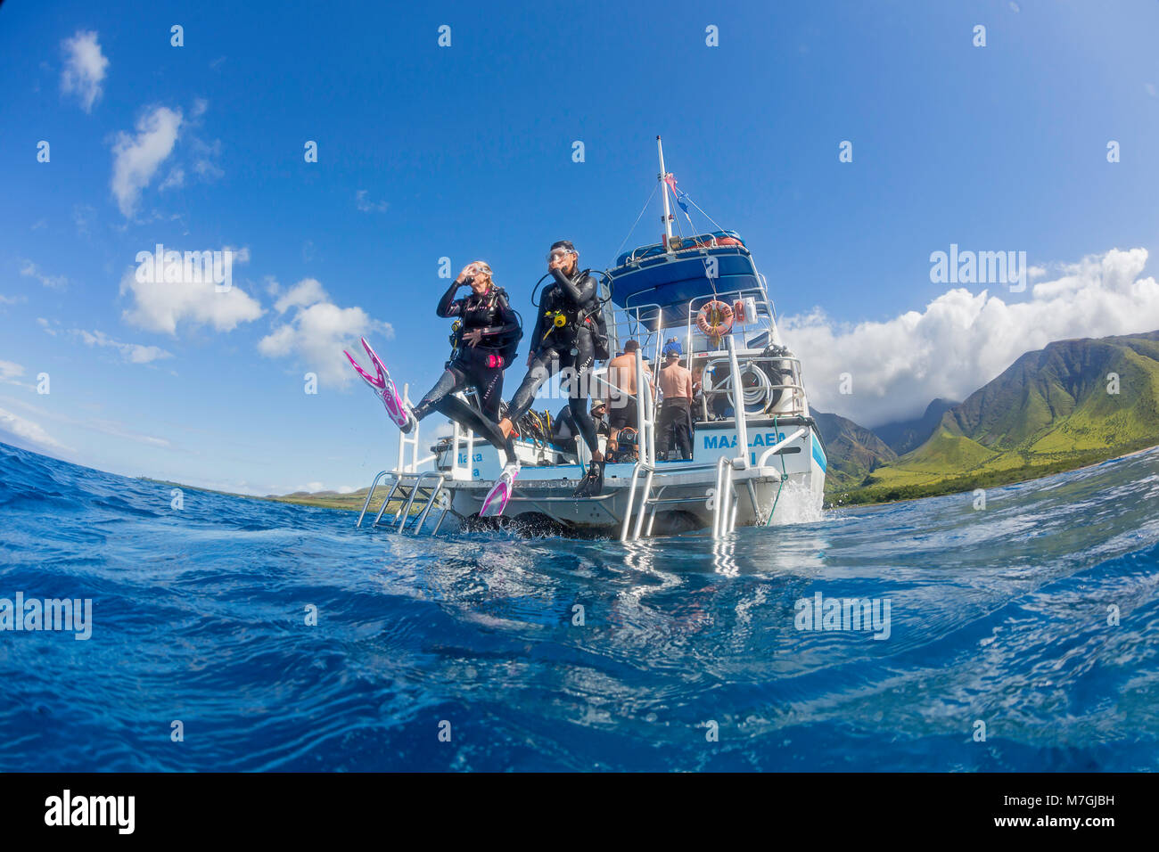 Divers (MR) step off a dive boat into the Pacific Ocean out from Ukumehame, Maui, Hawaii. - Stock Image