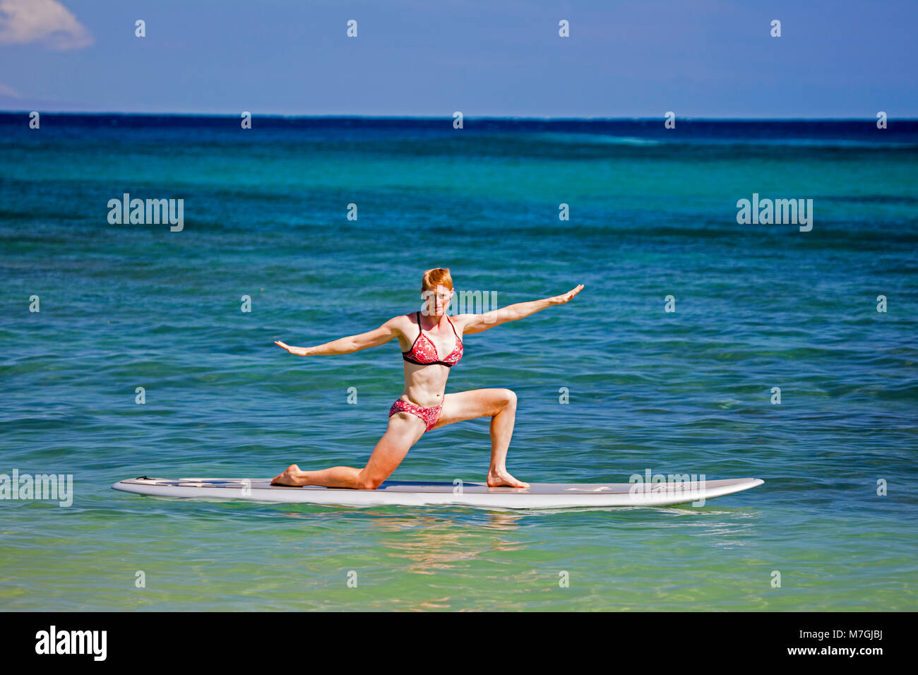 A woman on a stand-up paddle board in a yoga position, Maui, Hawaii. - Stock Image