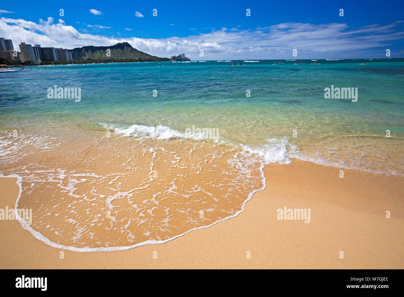 Waves wash up on Waikiki Beach with Diamond Head in the background, Oahu, Hawaii. - Stock Image