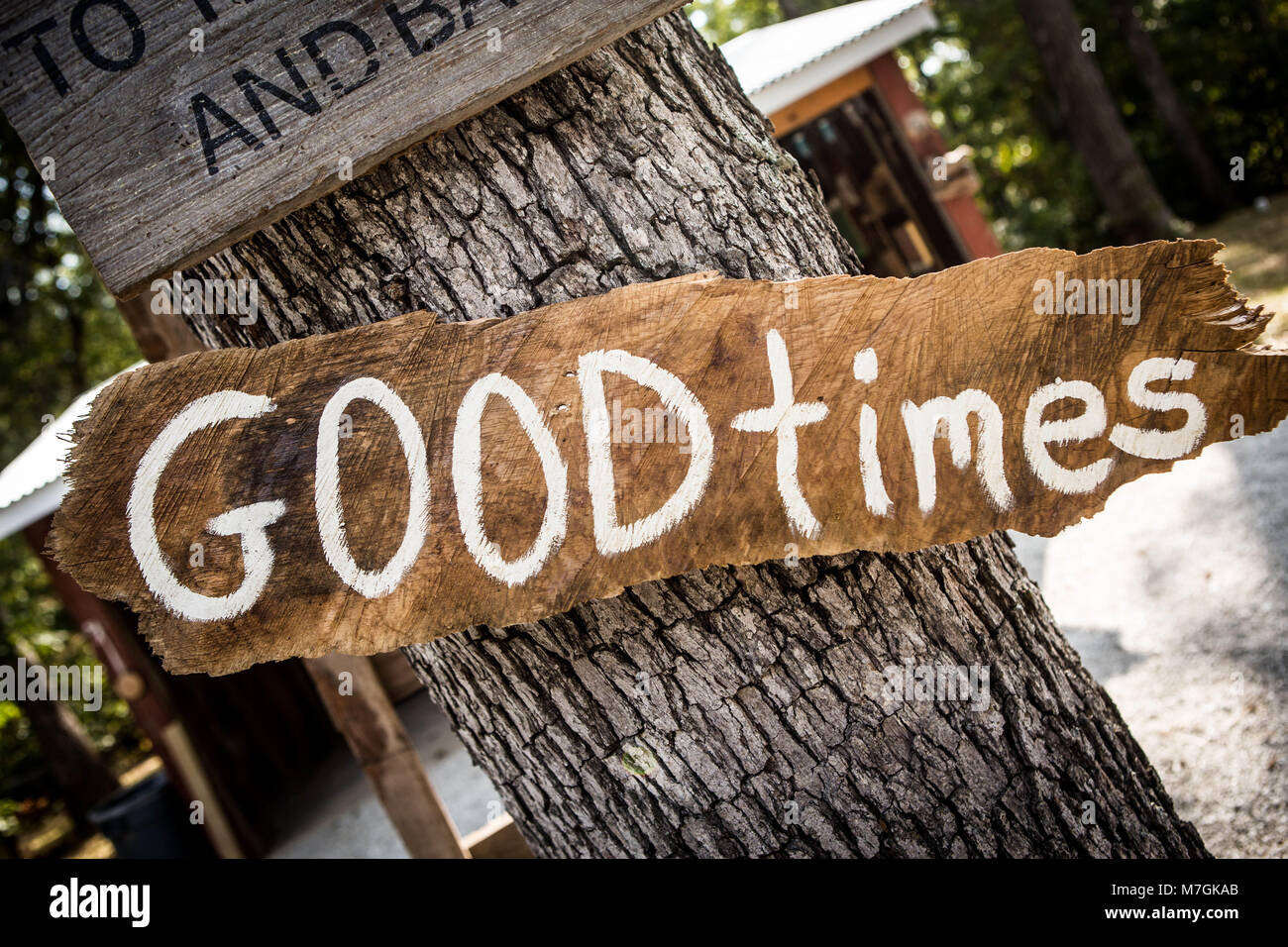 White Good Times hand painted sign on rough wooden board nailed to tree trunk in park or camping place - Stock Image