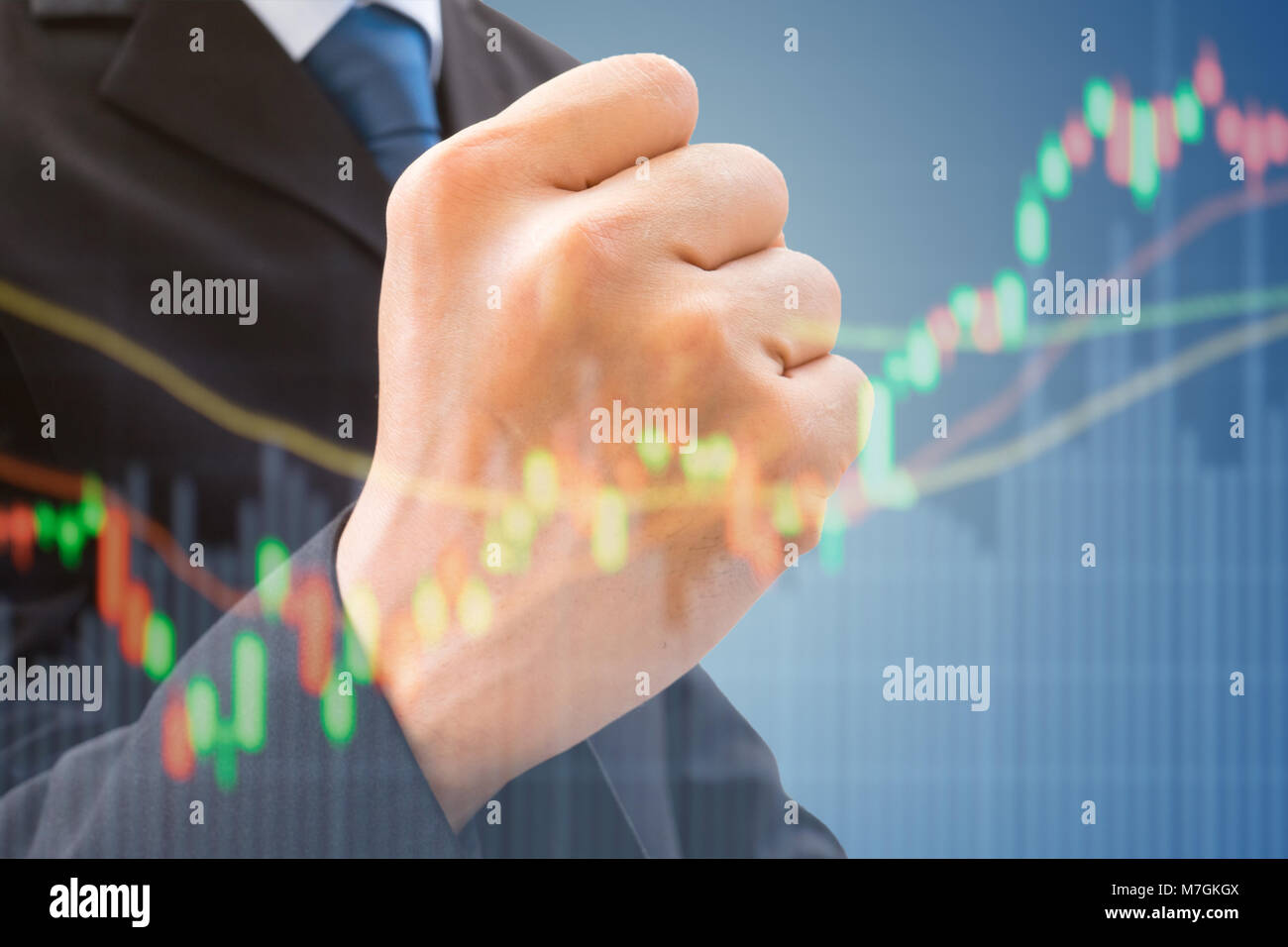 Businessman in dark gray suit raising his fist of successful and happiness in stock market rising and making profit - Stock Image