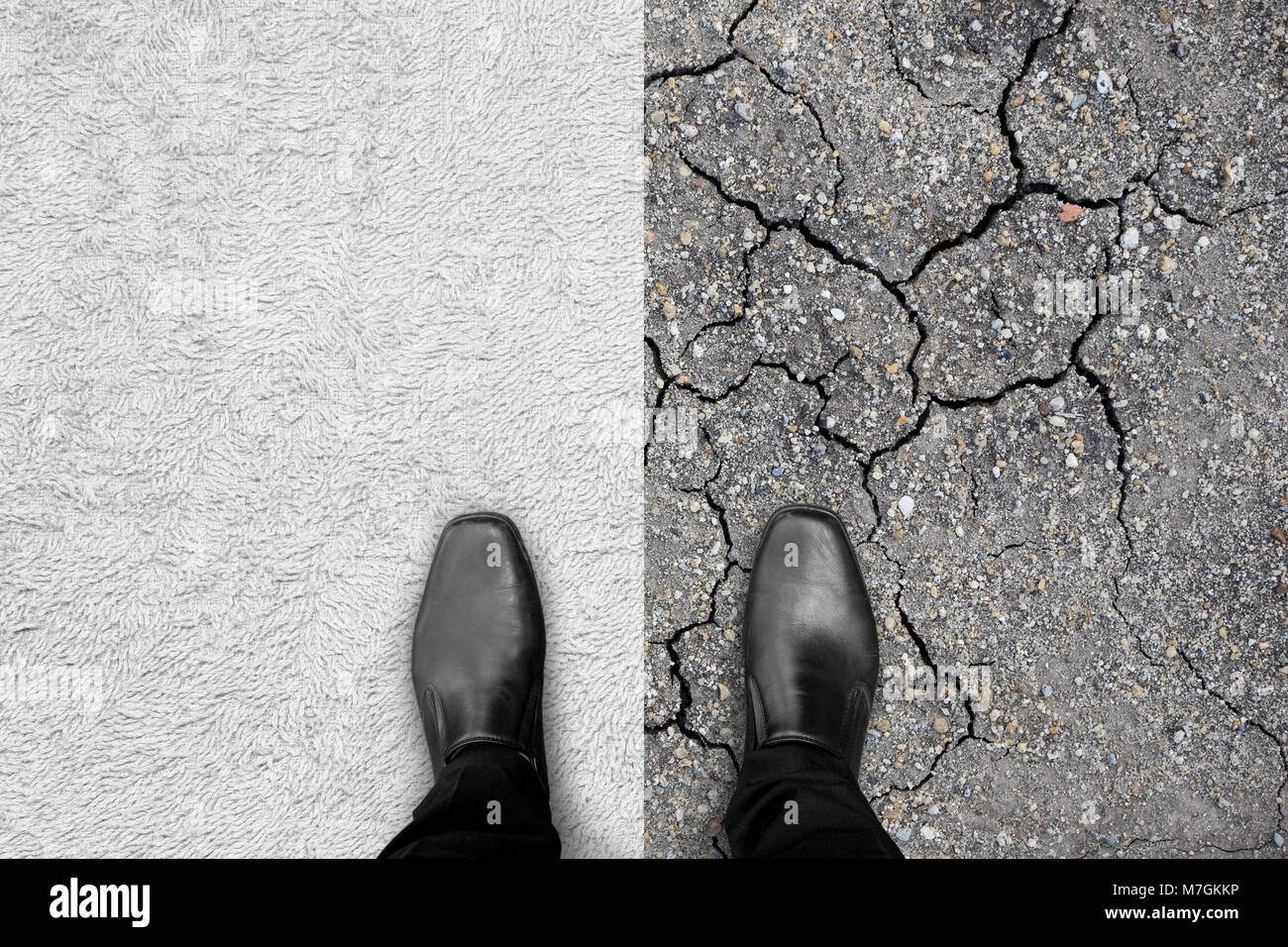 Black shoes standing, left foot on white carpet and right foot on dry earth. Represent two different ways like easy - Stock Image