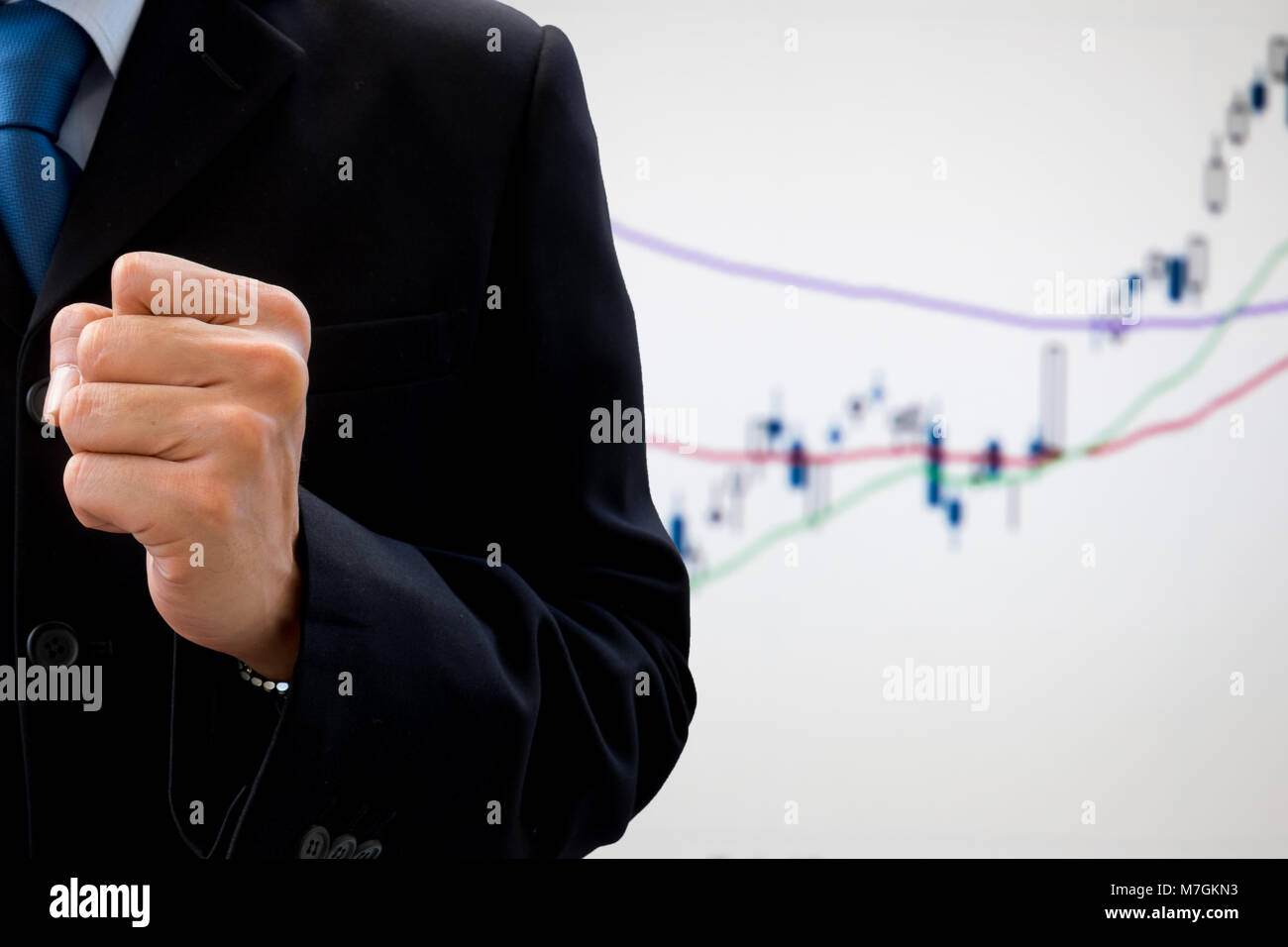 Businessman in dark gray suit raising his fist of success and victory in work or business. With economic and stock - Stock Image