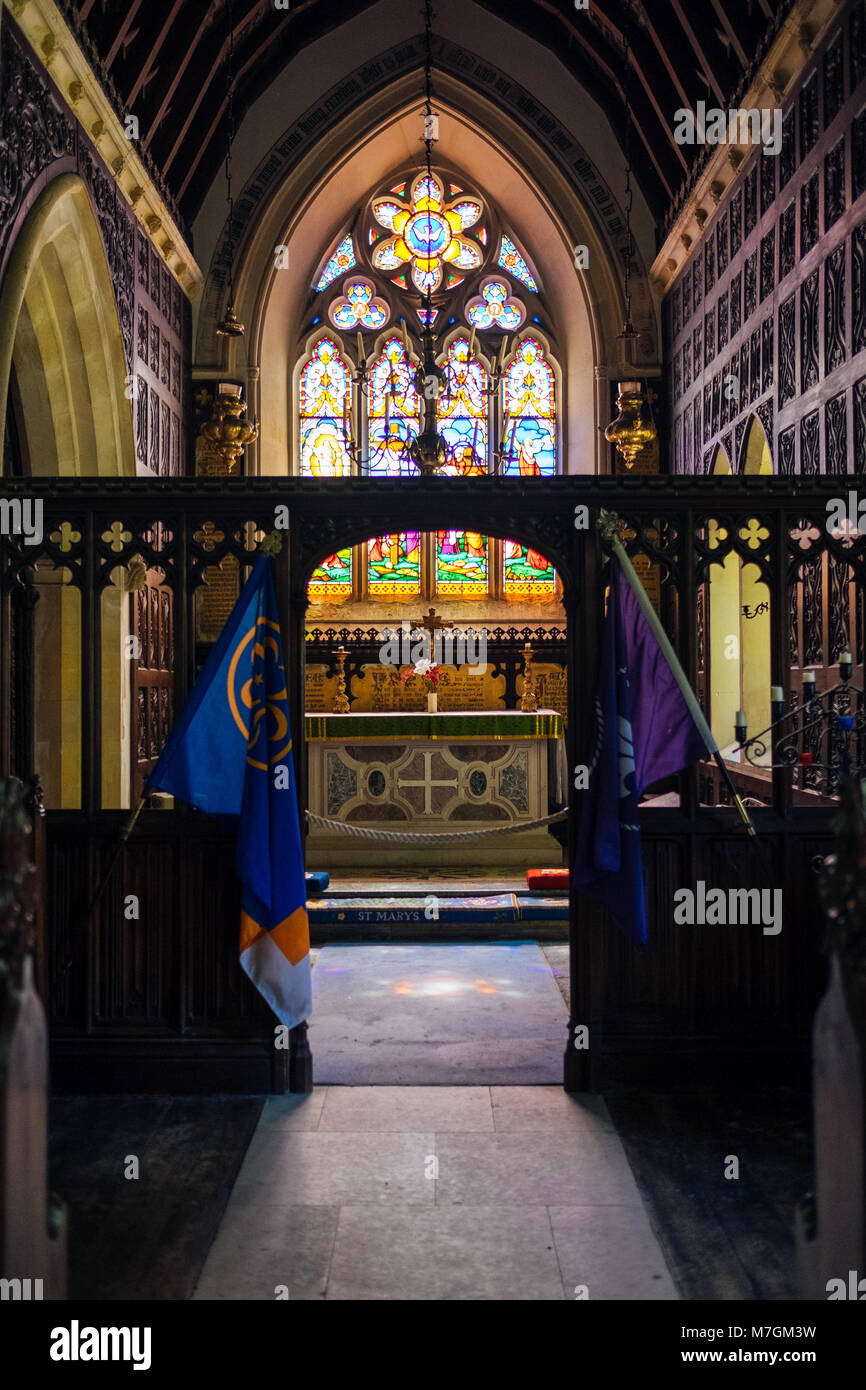 The beautiful stained glass window in St. Mary's church flanked by scout and guide flags, Brownsea Island, Poole, - Stock Image