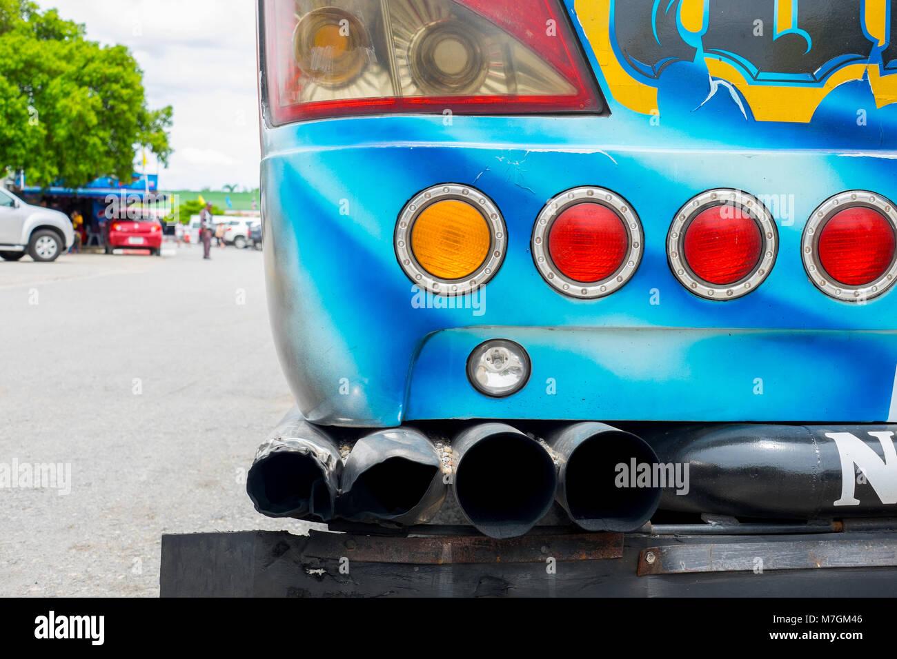 Rear side of tourist coach bus showing exhaust pip, left turn signal light, stop light, break light; backup light; Stock Photo
