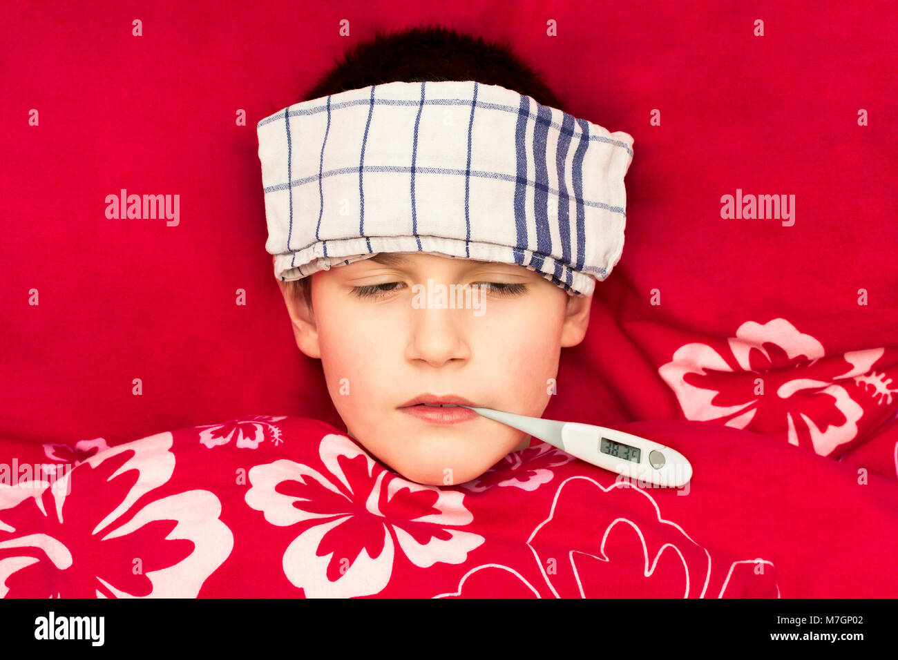 A sick boy lying in bed with a thermometer in his mouth. Cold compress on the forehead of a child. Influenza epidemic - Stock Image