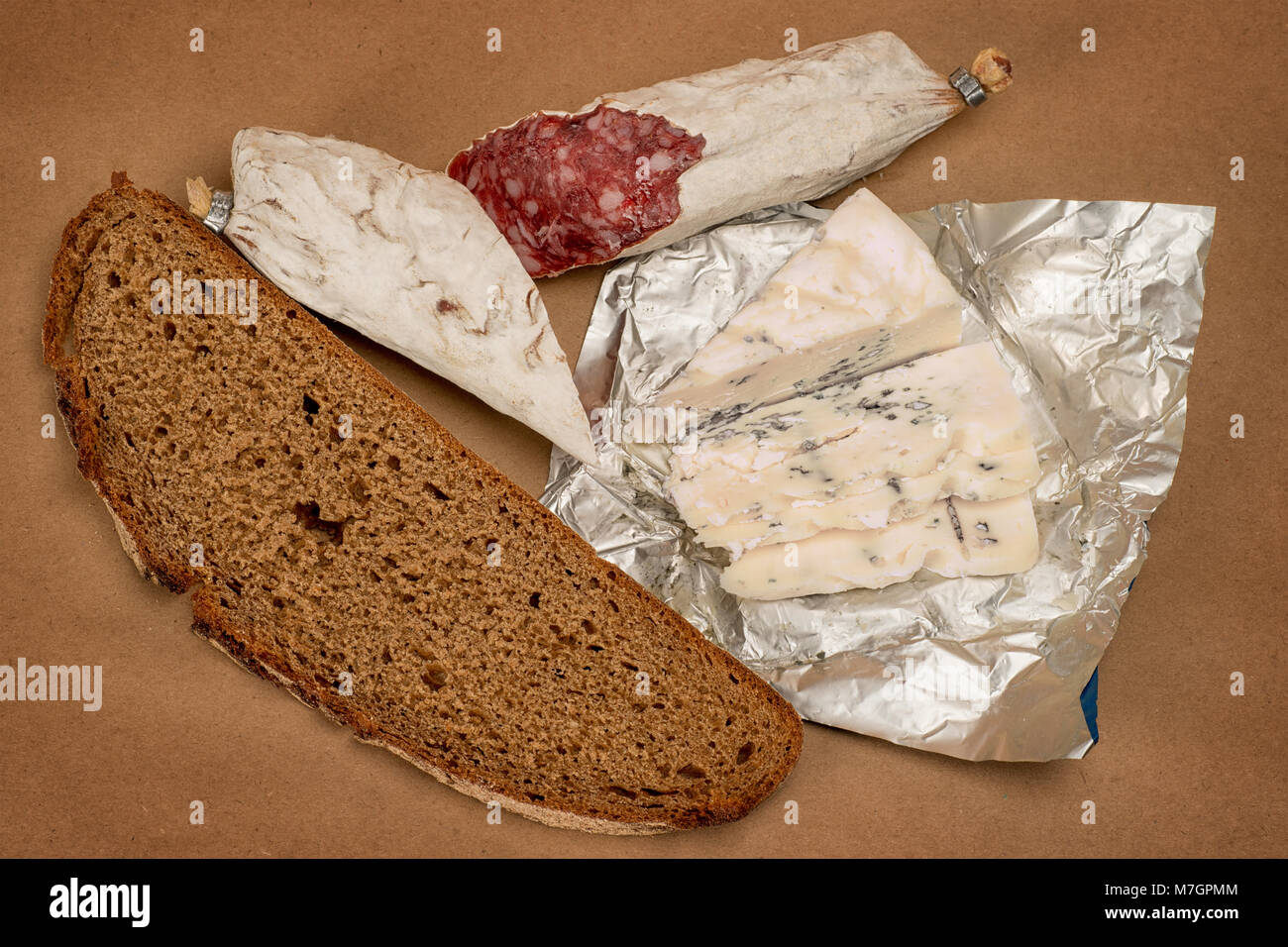 Breakfast theme still life. Bread, Roquefort cheese and smoked sausage on brown craft paper background - Stock Image