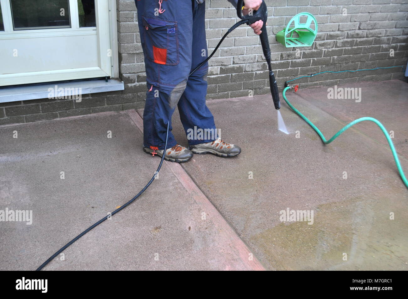 Spring yard work - man cleaning a sidewalk with a pressure washer. Man cleaning a sidewalk with a pressure washer - Stock Image