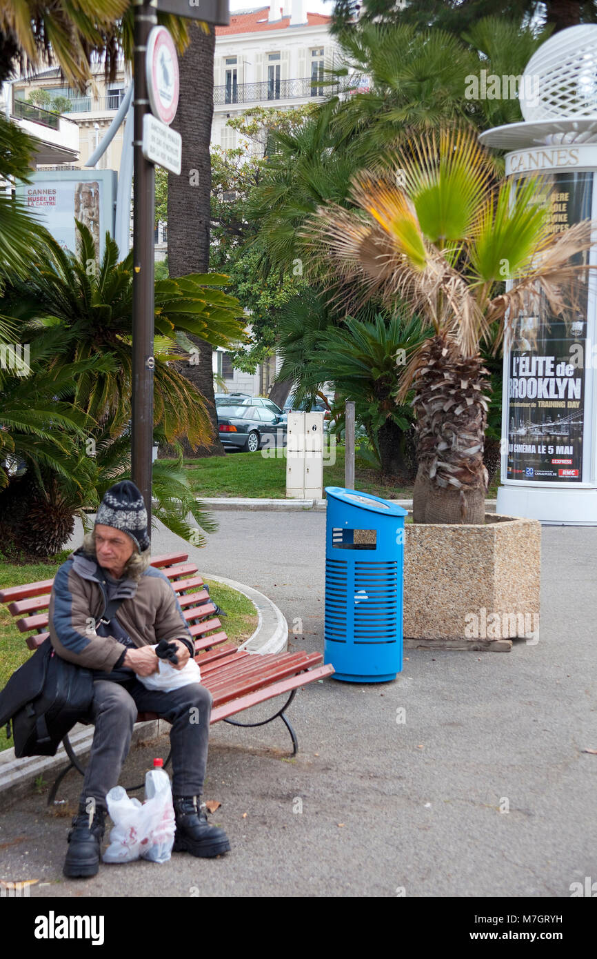 Poor homeless person sitting on a bench at Boulevard La Croisette, Cannes, french riviera, South France, France, - Stock Image