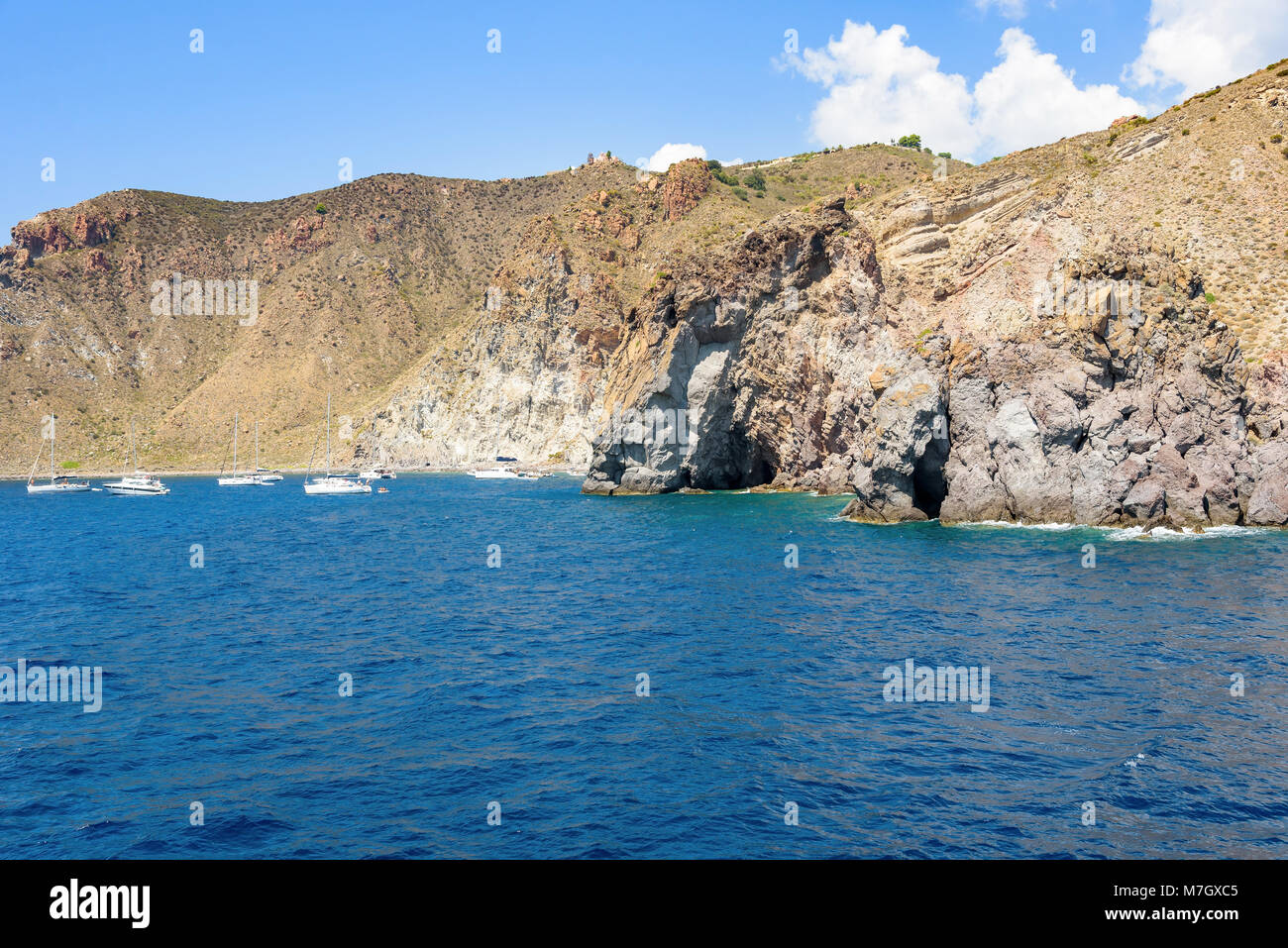 Yachts at the rocky coast of Lipari Island, Aeolian Islands, Italy Stock Photo