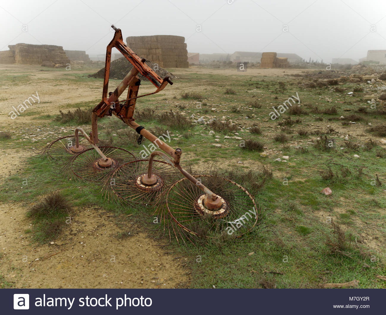 Close-up of a reaper in state of disuse for a prolonged period of time in a foggy day of winter. Zaragoza province, - Stock Image