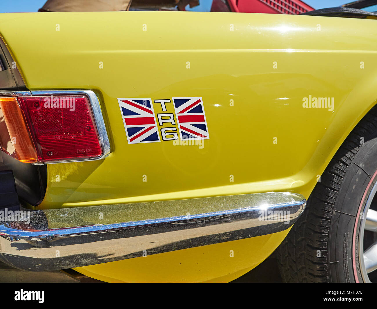 Right rear wing or quarter panel of 1985 British sports car Triumph TR6, painted yellow with Union Jack decal and - Stock Image