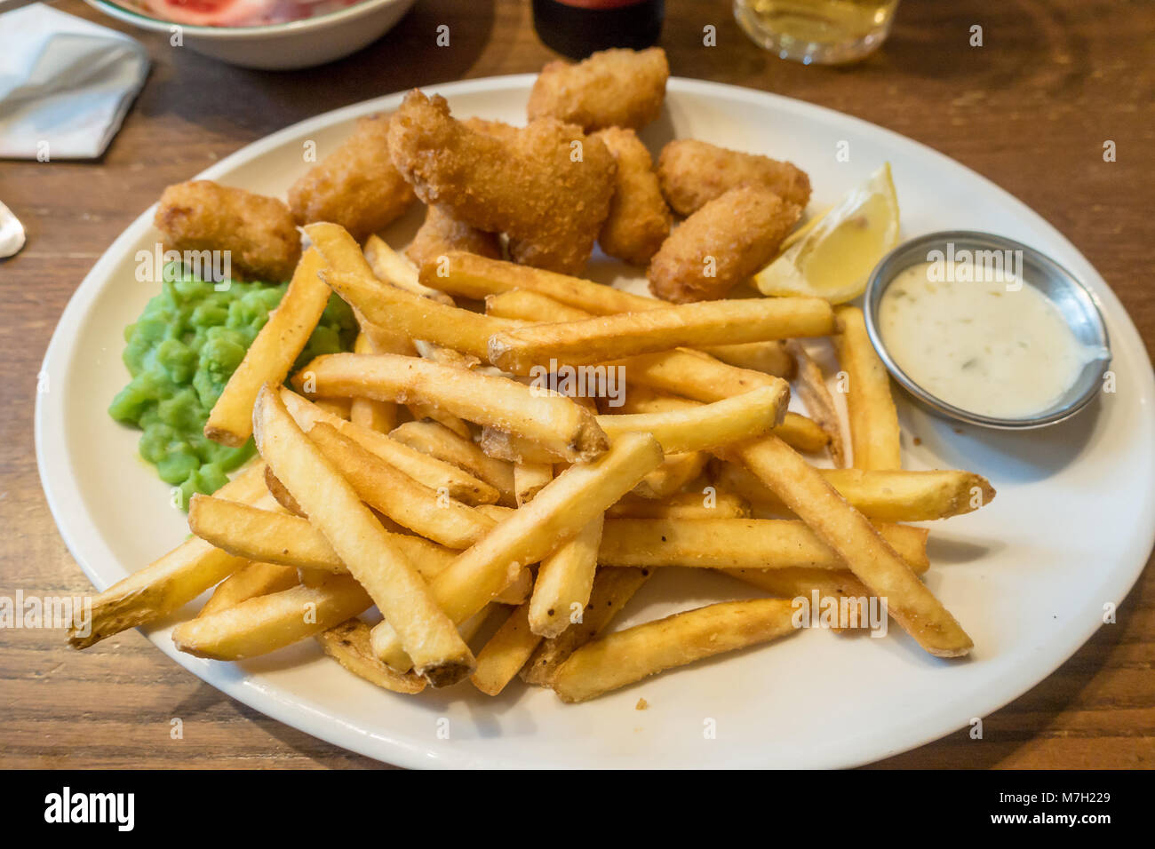 A plate of scampi, chips, mushy peas and tartar sauce. - Stock Image