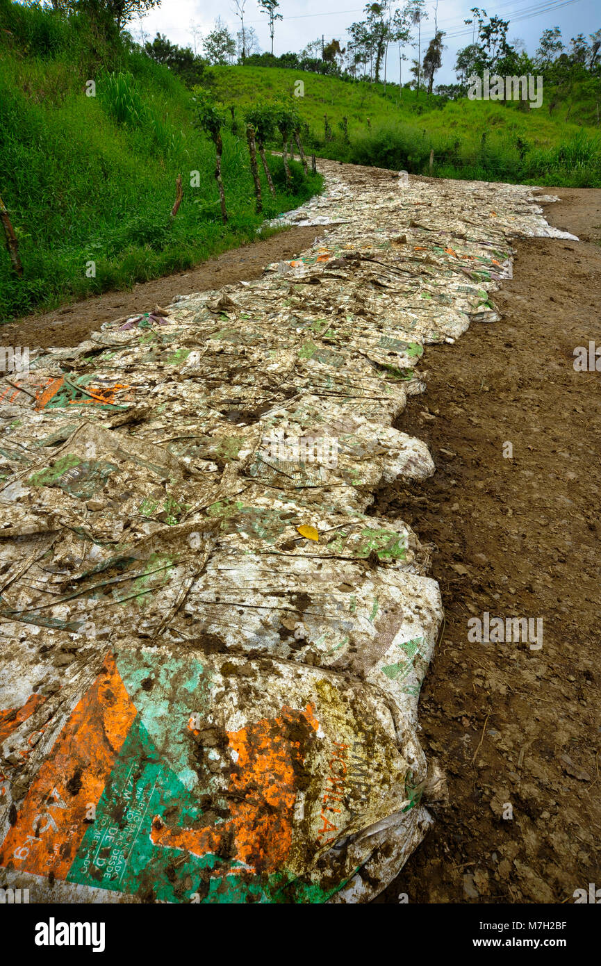 A dirt road covered in manure bags provides traction for vehicles in the Alajuela Province in Costa Rica. - Stock Image