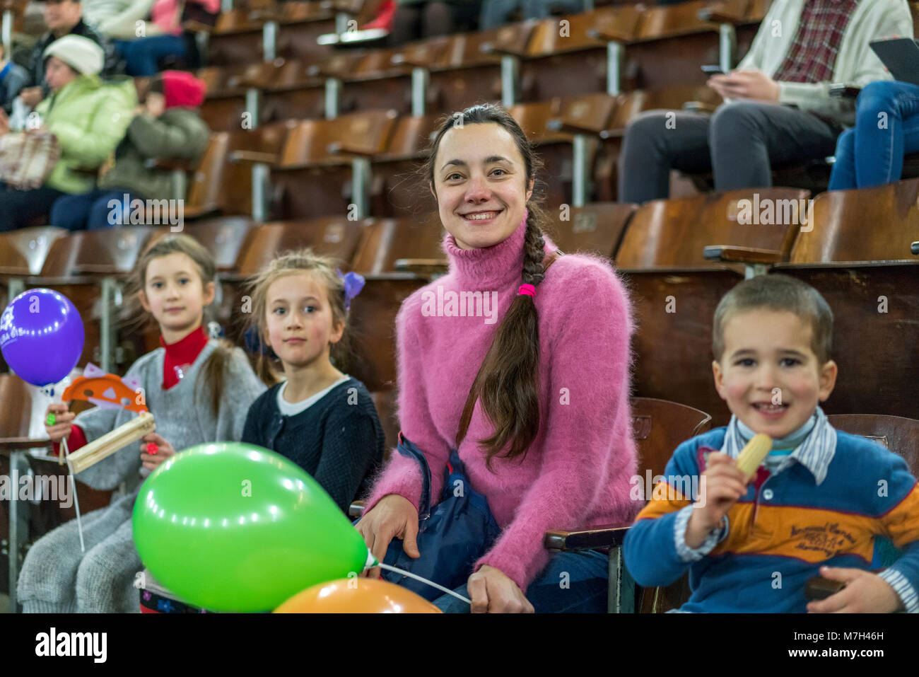 A mother with three children is sitting at a concert. Children with inflatable balls in the circus. Two sisters - Stock Image