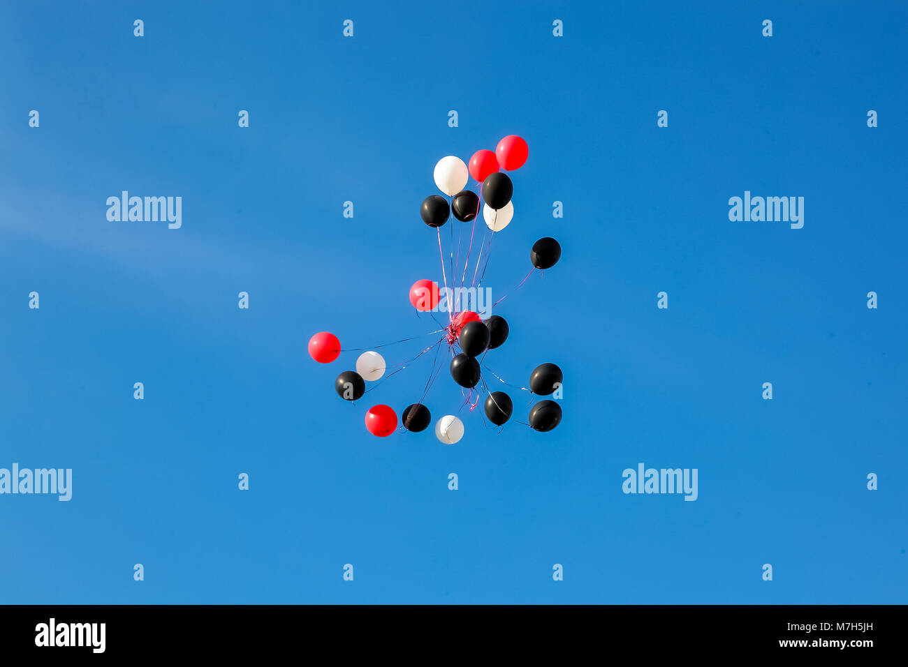 Red white black balloons floating away against a blue sky - Stock Image