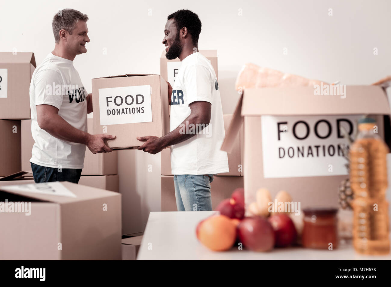 Delighted volunteers holding big parcel - Stock Image