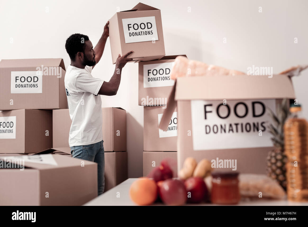 Serious volunteer collecting parcels with food - Stock Image