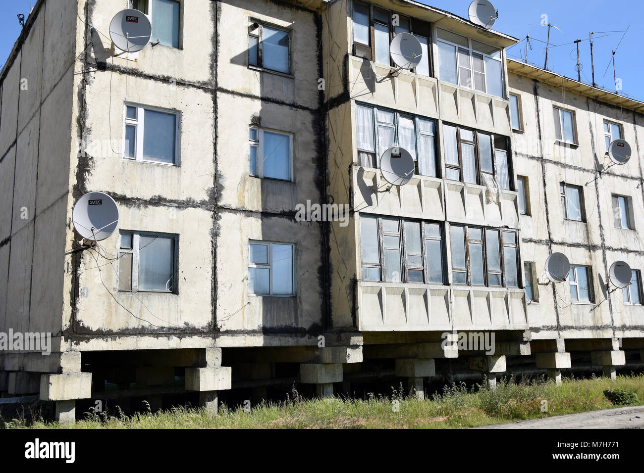 A concrete building in the town of Ust Nera, northern Kolyma. The building is built on piles because of the permafrost. - Stock Image