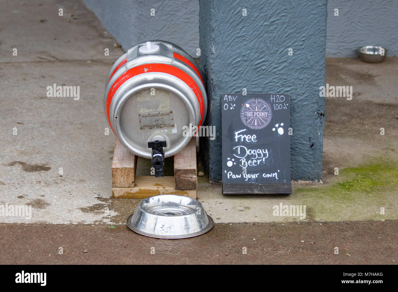 A beer keg barrel converted to pour water into a dog drinking bowl outside a pub with the words 'Free Doggy - Stock Image